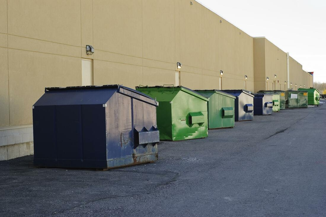 A bunch of commercial dumpsters in a line outside of a warehouse